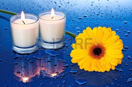 bloem bij kaarslicht met een reflectie op blauwe ondergrond